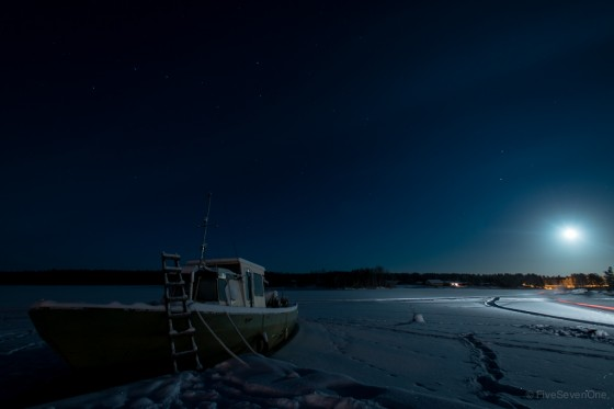 Boat frozen in Lake Inari with the Big Dipper over head in Nellim, Finland.